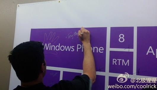 Employé de Microsoft signant l'affiche de la RTM de Windows Phone 8